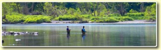 Two fishermen standing inside the creek.